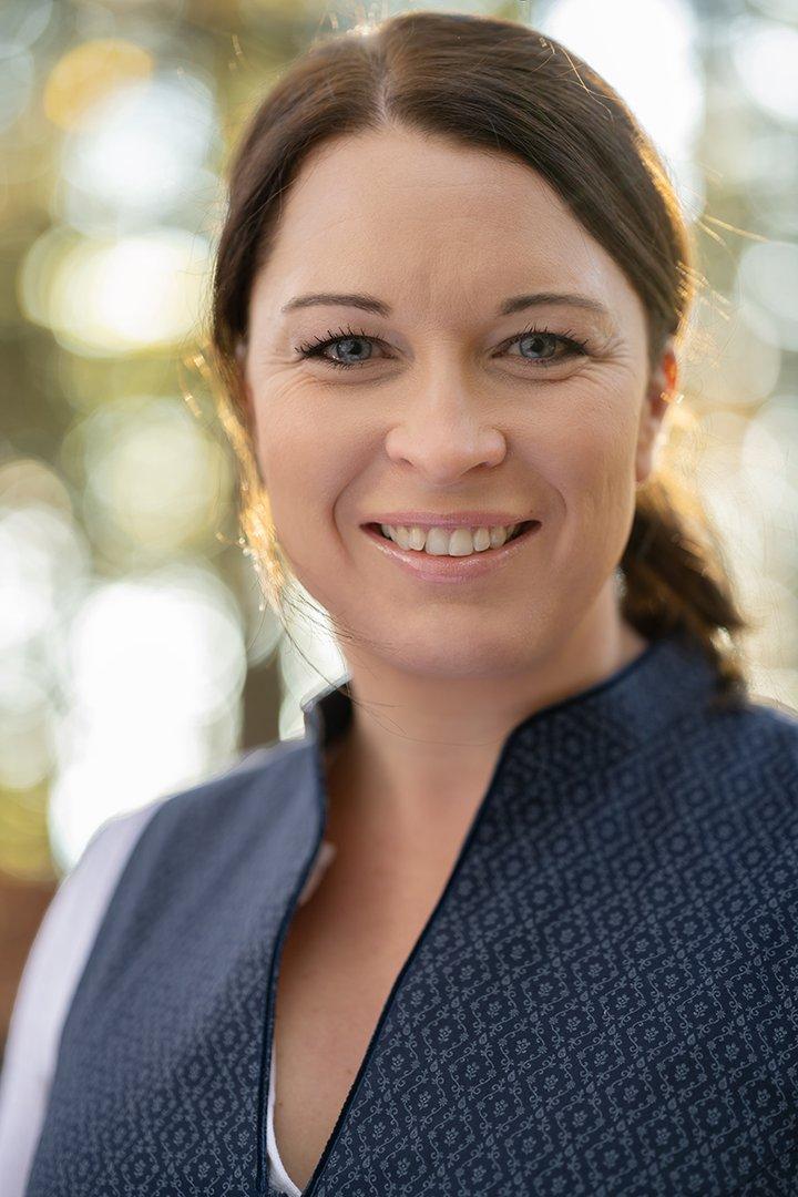 Portraitfoto von Hausruckwald-Teammitglied Bernadette Nagl. Dunkelbraune Haare zu einem Pferdeschwarz gebunden, dunkelblaues Dirndl mit Stehkragen und weißer, schlichter Bluse. Sie lächelt und schaut direkt in die Kamera.