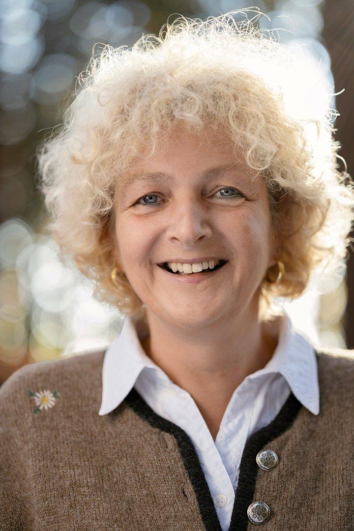 Portraitfoto von Hausruckwald-Teammitglied Brigitte Schiller. Hellblonde, kurze Locken. Beiger Trachtenjanker mit weißer Hemdbluse. Sie lächelt und schaut direkt in die Kamera.