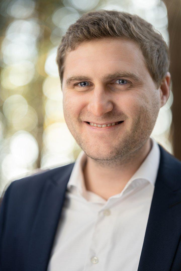 Portraitfoto von Hausruckwald-Geschäftsführer Elias Gavino-Schlager. Dunkelblonde, kurze Haare, dunkelblaue Anzugjacke und weißes Hemd, oberster Knopf offen. Er lächelt und schaut direkt in die Kamera.