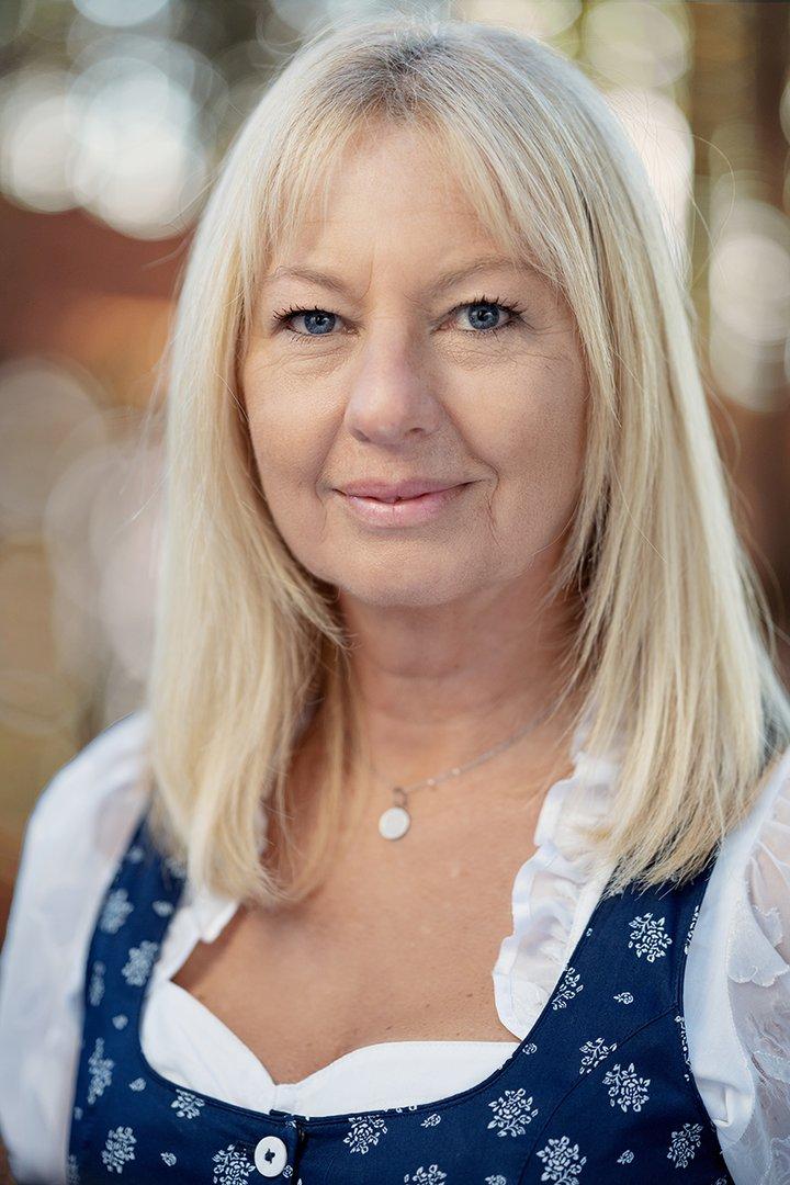 Portraitfoto von Hausruckwald-Teammitglied Karin Klement. Blonde, schulterlange Haare, dunkelblaues Dirndl mit weißer Rüschenbluse. Sie lächelt und schaut direkt in die Kamera.