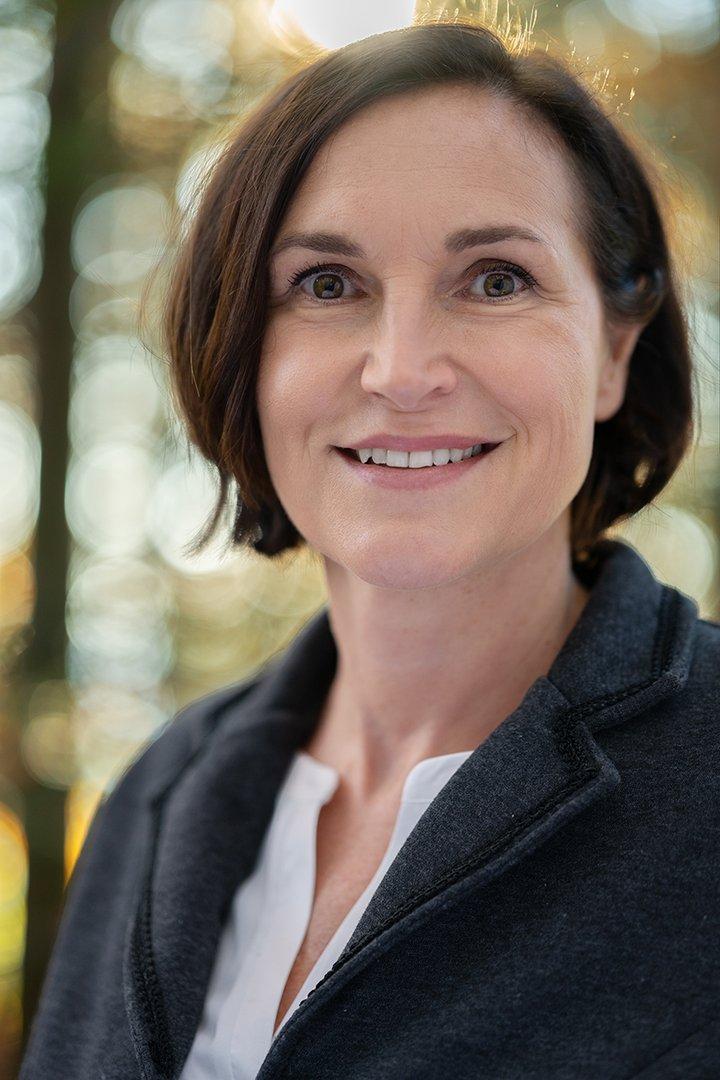 Portraitfoto von Hausruckwald-Teammitglied Martina Willeit. Dunkelbraune, kinnlange Haare, dunkelblaue Trachtenjacke mit weißer, schlichter Bluse. Sie lächelt und schaut direkt in die Kamera.