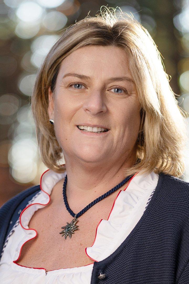 Portraitfoto von Hausruckwald-Teammitglied Michaela Scheibl. Blonde, kinnlange Haare, dunkelblaue Trachtenweste mit weißer, Dirndlbluse darunter. Sie lächelt und schaut direkt in die Kamera.